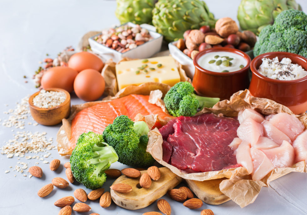 Assortment of healthy protein source and body building food. Meat beef salmon chicken breast eggs dairy products cheese yogurt beans artichokes broccoli nuts oat meal